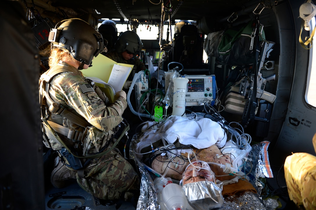 U.S. Army Sgt. Megan Smith, 159th Combat Aviation Brigade medic, reviews a patient's medical records during a patient transfer in Afghanistan, July 2014. Smith is a Devils Lake, North Dakota native deployed from Fort Campbell, Ky. Medevac typically flies with two aircraft and a team of four and may include a fifth with an en route care nurse. (U.S. Air Force photo by Senior Airman Sandra Welch)