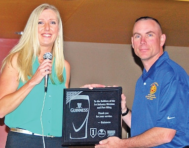 Amanda Yates, military sales and marketing analyst, Diageo Guinness USA, left, presents Fort Riley Garrison Command Sgt. Maj. Jason Schmidt, right, with a plaque thanking Fort Riley Soldiers for their service during halftime of the 2014 FIFA World Cup final match July 13 at the Warrior Zone.  Representatives from Guinness were on hand to raise a glass to Soldiers during the viewing party.