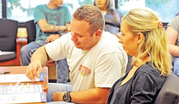 Sgt. Steven Jones, 1st Bn., 63rd Armor Regt., left, and his wife Brianna Jones, right, play marriage bingo at the start of a ScreamFree Marriage class July 10 at CYSS Parent Central.