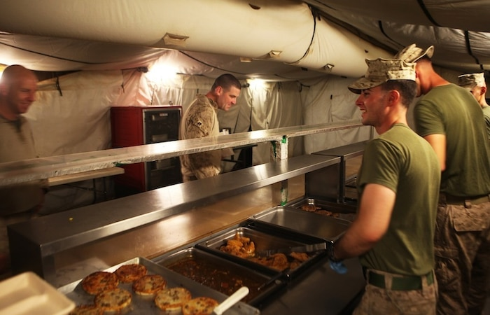 Food service specialists with 1st Battalion, 7th Marine Regiment, prepare to serve troops at the Harvest Falcon dining facility aboard Camp Dwyer, Helmand province, Afghanistan, July 21, 2014. The food service Marines at the Harvest Falcon are in charge of making sure meals are served at the correct temperature, the facility is cleaned daily and food is cooked properly for every meal. (U.S. Marine Corps photo by Cpl. Cody Haas/ Released)