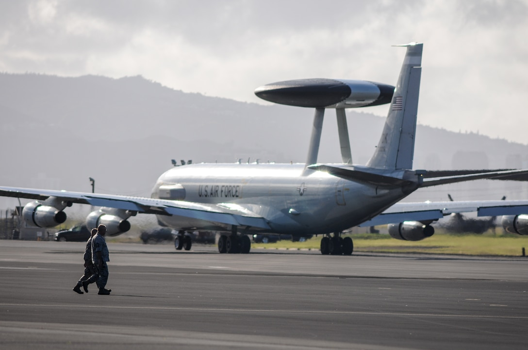 Airmen cross the flight line behind an E-3 Sentry Airborne Warning and Control System aircraft flown by Airmen from the 513th Air Control Group at Tinker Air Force Base, Oklahoma, on July 24 at Joint Base Pearl Harbor-Hickam, Hawaii. More than 60 reservists from the 513th Air Control Group traveled from Tinker to participate in the Rim of the Pacific, or RIMPAC, 2014 exercise, the world's largest maritime exercise held biannually in and around the Hawaiian islands. (U.S. Air Force photo by Staff Sgt. Caleb Wanzer)