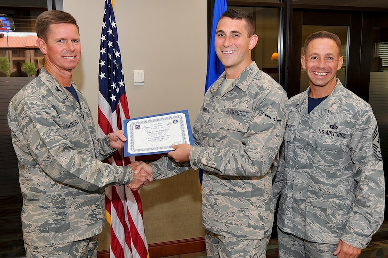 PETERSON AIR FORCE BASE, Colo. — Airman Johnathon Downs (center), poses for a photo while being presented an FTAC certificate of completion July 25 from Col. Richard Burchfield, Individual Mobilization Augmentee to the commander, and Chief Master Sgt. Richard Redman, former 21st SW command chief. (U.S. Air Force photo/Airman 1st Class Rose Gudex)