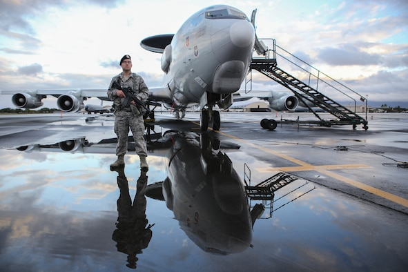 Staff Sgt. Robert Abbey, assigned to the 507th Security Forces Squadron at Tinker Air Force Base, Okla., guards an E-3 Sentry on July 20 on the flight line at Joint Base Pearl Harbor-Hickam, Hawaii. Security forces Airmen from the 507th are supporting reservists from the 513th Air Control Group as they fly missions in support of the Rim of the Pacific 2014 exercise. (U.S. Air Force photo by Staff Sgt. Caleb Wanzer)