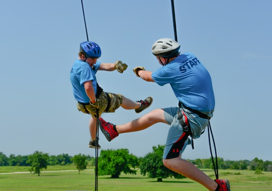 Jake January and Garret Poindexter, youth volunteer leaders at Kids Kamp, celebrate while rappelling a 35-foot tower at Camp Gruber, Braggs, Okla., July 21, 2014. The camp hosts children of Oklahoma National Guard members and implements Army and Air Force core values. (U.S. Air Force photo by Airman 1st Class Tyler Woodward/Released)