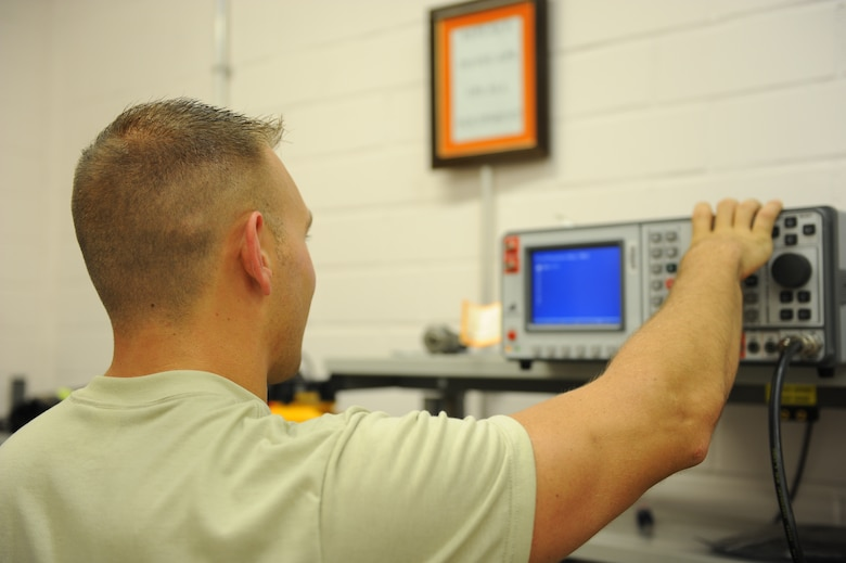 U.S. Air Force Airman 1st Class Ryan Macri, a 606th Air Control Squadron radio frequency transmission journeyman from New Castle, Pa., configures a machine that tests and ejects radio frequency signals July 30, 2014, at his squadron at Spangdahlem Air Base, Germany. The 606th ACS is the only squadron of its kind in Europe. (U.S. Air Force photo by Airman 1st Class Dylan Nuckolls/Released)