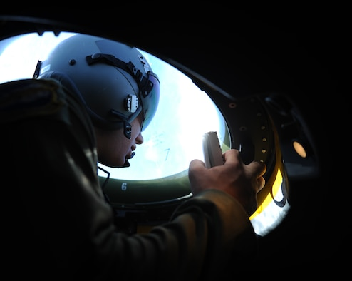Airman 1st Class Jacob Betts, 40th Airlift Squadron loadmaster, watches an F-16 Fighting Falcon from a bubbled window on board a C-130J Super Hercules July 23, 2014, en route to Naval Air Station Joint Reserve Base Fort Worth, Texas. During a training exercise, C-130J pilots reacted to the movements of the F-16 and maneuvered to ensure the safety of their aircraft. (U.S. Air Force photo by Airman 1st Class Kedesha Pennant)