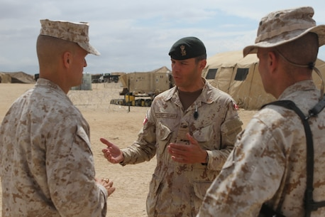 Col. Dani Fortin, commander of adjacent Canadian Forces, 5 Canadian Mechanized Brigade Group, discusses operations to be conducted in the following weeks with Brig. Gen. Carl E. Mundy III, commanding general of 1st Marine Expeditionary Brigade, during Large Scale Exercise 2014 aboard Marine Corps Air Ground Combat Center Twentynine Palms, Calif., Aug. 3, 2014. LSE-14 is a bilateral training exercise being conducted by 1st MEB to build U.S. and Canadian forces' joint capabilities through live, simulated, and constructive military training activities from Aug. 8-14. (U.S. Marine Corps photo by Lance Cpl. Angel Serna/Released)