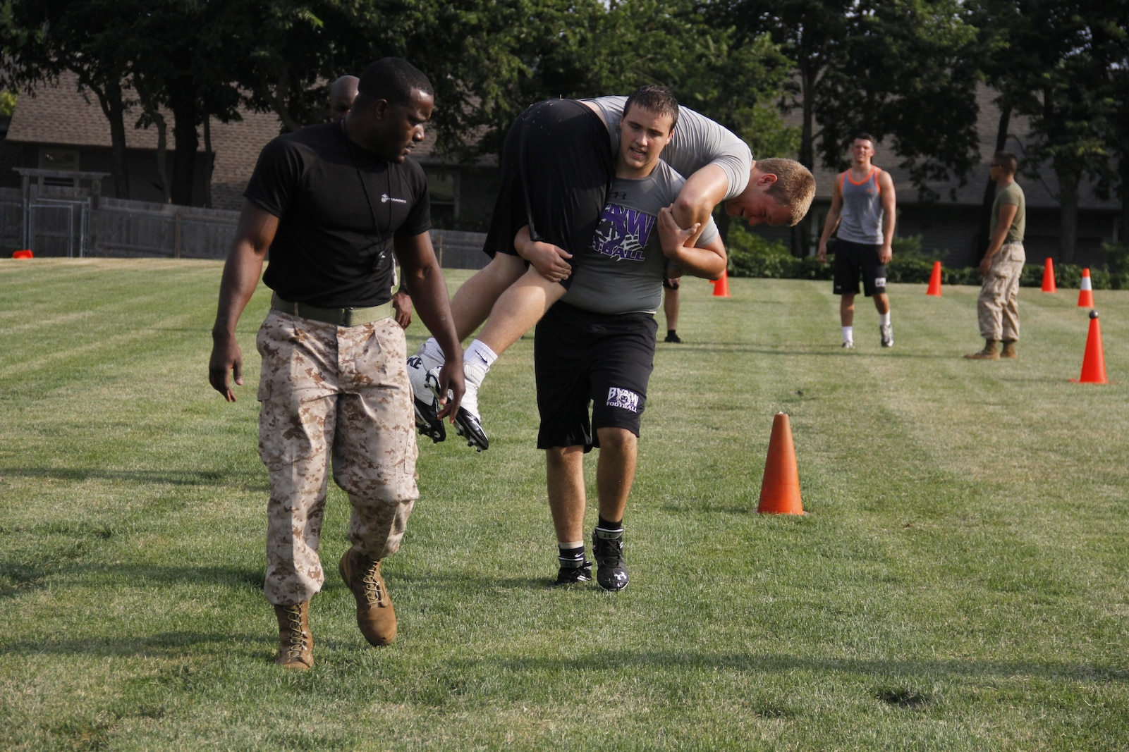Eric W. Naulty, a junior Blue Valley Northwest High School Huskies offensive guard and defensive tackle, fireman carries Jack J. Kutey, a senior Huskies defensive end, as Sgt. Laronald R. McKinney, a Marine Corps Recruiting Station Kansas City, Recruiting Sub-Station Olathe recruiter, encourages Naulty to push through at the Huskies' practice field Aug. 5, 2014 during the Combat Fitness Test. The fireman carry makes up the maneuver-under-fire portion of the CFT and participants must perform pushups, a high and low crawl, cone-agility drills, a buddy drag, throw a dummy grenade, and finish with a sprint, carrying 30-pound ammunition cans.