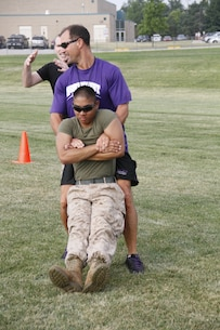 Mike H. Zegunis, the Blue Valley Northwest High School Huskies' head football coach, buddy drags Lance Cpl. Dominic P. Ehretmounivong, a Detachment 2, Supply Company, Combat Logistics Battalion 453 warehouse clerk, to demonstrate the proper way to buddy drag to his players as Staff Sgt. Paul D. Bush, background, the Marine Corps Recruiting Station Kansas City, Recruiting Sub-Station Olathe staff noncomissioned officer-in-charge, advises on proper technique at the Huskies' practice field Aug. 5, 2014.