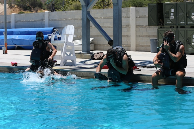 Special Amphibious Reconnaissance Corpsman enter the water pool side, during proficiency dive training aboard Camp Pendleton, Calif., July 22. The SARCs were supported by Navy Divers from 1st Reconstruction consolidated dive locker.