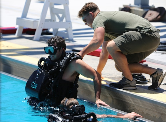 A Navy Diver aids a Special Amphibious Reconnaissance Corpsman exit a pool during proficiency dive training aboard Camp Pendleton, Calif., July 22. The SARCs were supported by Navy Divers from 1st Reconstruction consolidated dive locker.