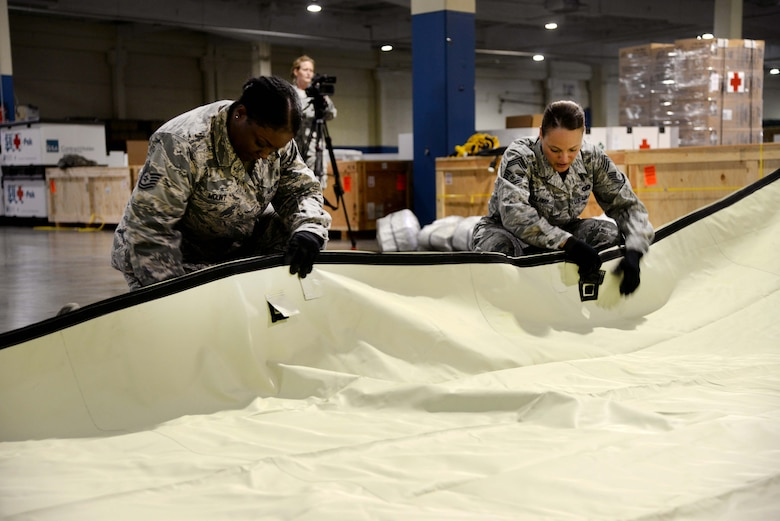 Tech. Sgt. Lakisha Mount, 937th Training Support Squadron, and Chief Master Sgt. Laura Callaway, 559th Medical Group superintendent, secure the tarp of an Alaskan Shelter tent during a tent-building exercise July 21, 2014 on Port San Antonio, Texas. The exercise served as training for the wing's Defense CBRN Response Force. The team is tasked to provide medical support in the event of a major natural disaster or attack occurring within the U.S. (U.S. Air Force photo/Staff Sgt. Jerilyn Quintanilla)