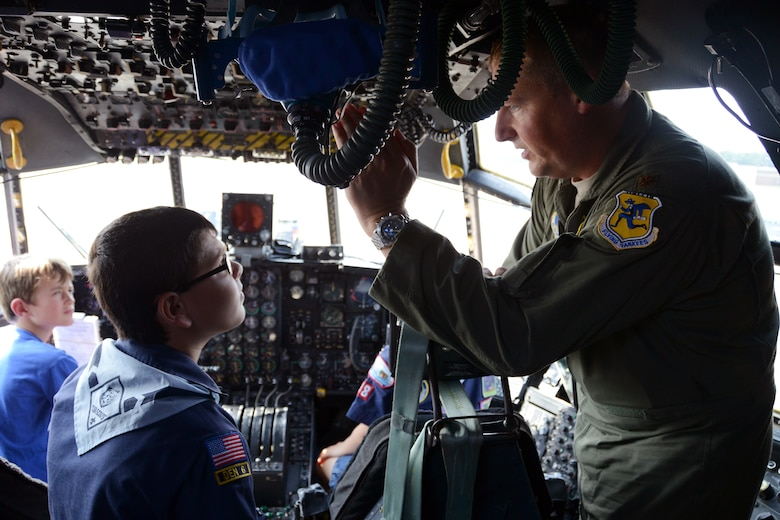 Maj. Kevin Eikleberry, pilot for the 118th Airlift Squadron, explains the various functions of the C-130H aircraft controls to a very intent Anthony Maio, 9, as Blake Kamoen, 8, listens in. Behind Eikleberry in the co-pilot seat is Tristan Schemmerling, 8. All three of the children are part of Cub Scout Troop 18 and came to the Bradley Air National Guard Base, East Granby, Conn., Aug. 4, 2014, to take a tour of the unit's recently assigned aircraft. (U.S. Air National Guard photo by Tech. Sgt. Joshua Mead/Released)