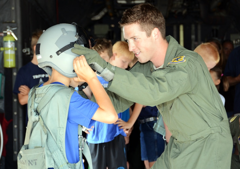 Staff Sgt. Daniel Haynes, a loadmaster with the 118th Airlift Squadron, adjusts an aviation helmet on Cub Scout Blake Kamoen, 8, during a base tour at Bradley Air National Guard Base in East Granby, Conn., Aug. 4, 2014. Haynes later said that tours like these are part of the reason he joined the Air Force. (U.S. Air National Guard photo by Tech. Sgt. Joshua Mead/Released)