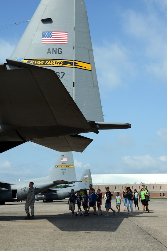 Maj. Bryon Turner, public affairs officer with the 103rd Airlift Wing, leads a group of Cub Scouts out to a C-130H Hercules aircraft on the flightline at Bradley Air National Guard Base, East Granby, Conn., Aug. 4, 2014. The Cub Scouts were able to climb into the cockpit of the aircraft and don some equipment used by the loadmasters. (U.S. Air National Guard photo by Tech. Sgt. Joshua Mead/Released)