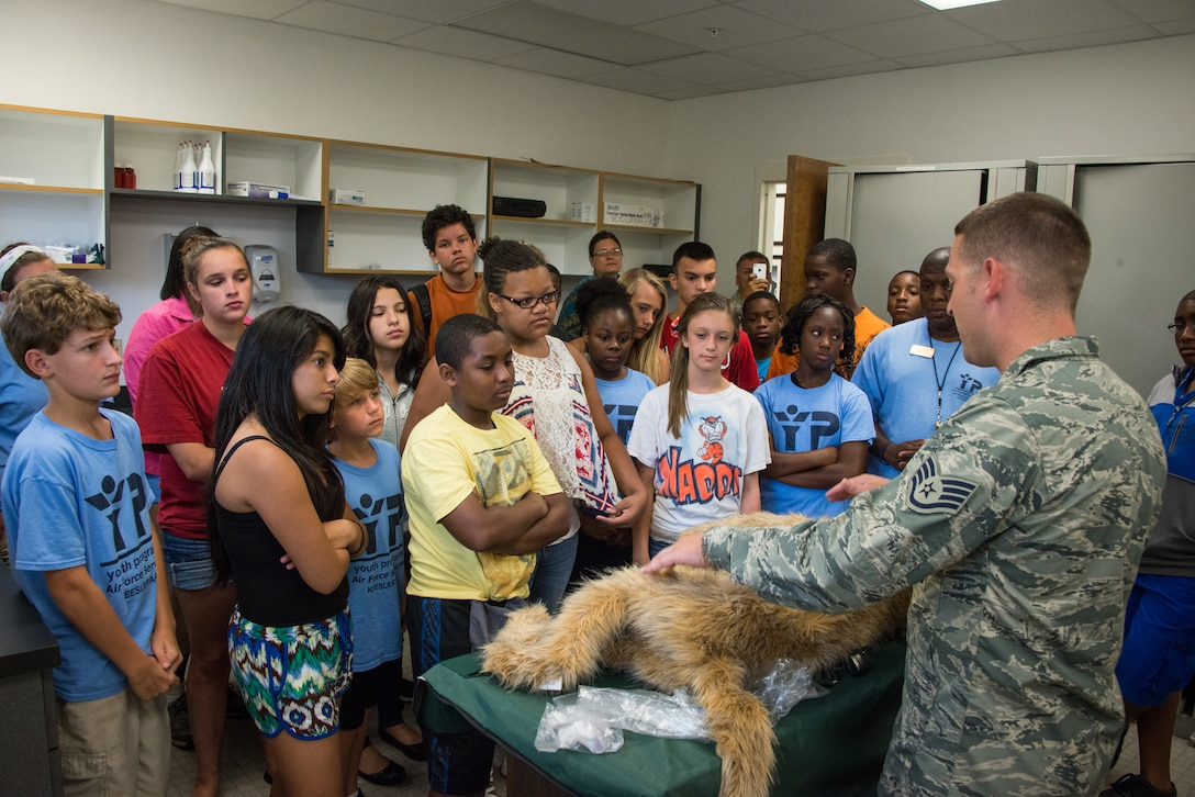 Staff Sgt. James Martin, 81st Security Forces Squadron, explains to children of Keesler personnel how a simulated dog is used to practice veterinary procedures for military working dogs at the K-9 facility Aug. 1, 2014, at Keesler Air Force Base, Miss. Children from the child development center and the youth center participated in the tour.  (U.S. Air Force photo by Marie Floyd)