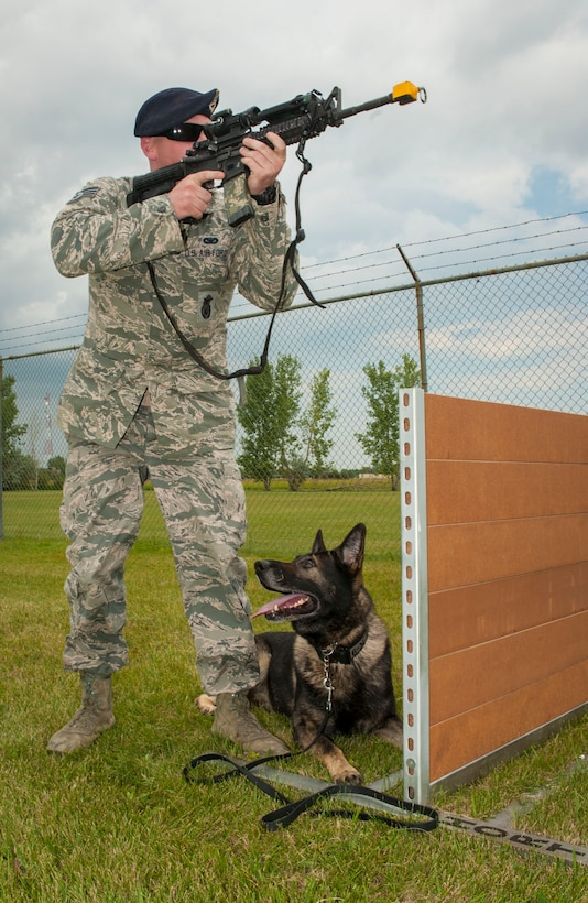 Staff Sgt. Tim Glover, a 5th Security Forces Squadron military working dog handler, completes weapons training with his MWD Roko July 28, 2014, on Minot Air Force Base, N.D. During training, Glover used blank rounds to test Roko's reaction to the sound of gunfire and his ability to obey commands in a stressful environment. (U.S. Air Force photo/Senior Airman Stephanie Morris)