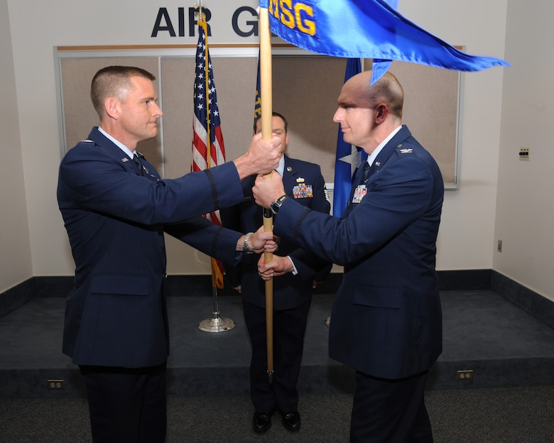 Col. Rick Wedan, 142nd Fighter Wing Commander, left, exchanges the colors with outgoing 142nd MSG Commander Col. Paul Fitzgerald, right, during the Mission Support Group Change of Command Ceremony, Portland Air National Guard Base, Ore., Aug. 3, 2014. (U.S. Air National Guard photo by Tech. Sgt. John Hughel, 142nd Fighter Wing Public Affairs/Released)