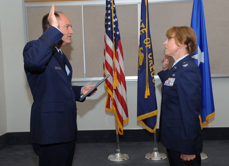 Brig. Gen. Michael Stencel, Commander of the Oregon Air National Guard, left, reaffirms the officer's oath to newly promoted Col. Donna Prigmore during her promotion ceremony held at the Portland Air National Guard Base, Ore., Aug. 3, 2014. (U.S. Air National Guard photo by Tech. Sgt. John Hughel, 142nd Fighter Wing Public Affairs/Released)