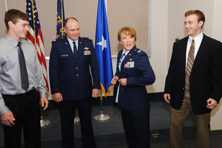 Newly promoted Colonel Donna Prigmore don a jacket bearing the colonel insignia with the assistance of her husband Lt. Col. John Prigmore, during her promotion ceremony held at the Portland Air National Guard Base, Ore., Aug. 3, 2014. (U.S. Air National Guard photo by Tech. Sgt. John Hughel, 142nd Fighter Wing Public Affairs/Released)
