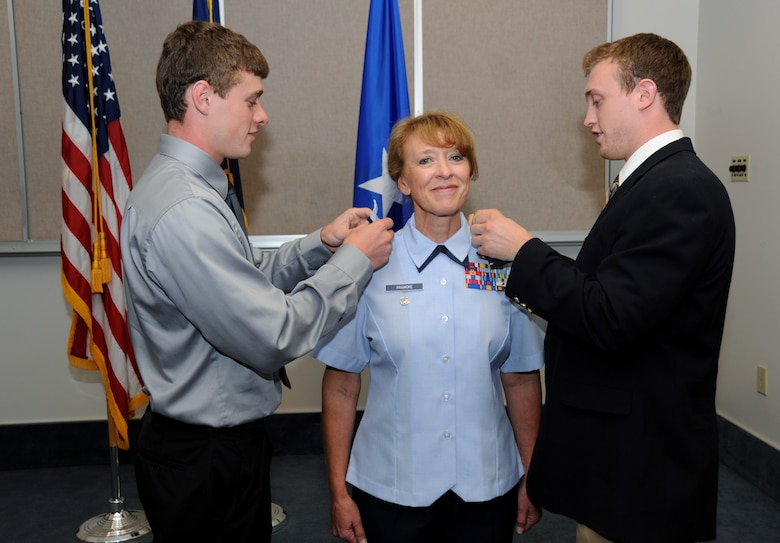 Lt. Col. Donna Prigmore is promoted to the rank of Colonel with the assistance of her two sons, Brian and Nathan Prigmore, during her promotion ceremony held at the Portland Air National Guard Base, Ore., Aug. 3, 2014. (U.S. Air National Guard photo by Tech. Sgt. John Hughel, 142nd Fighter Wing Public Affairs/Released)