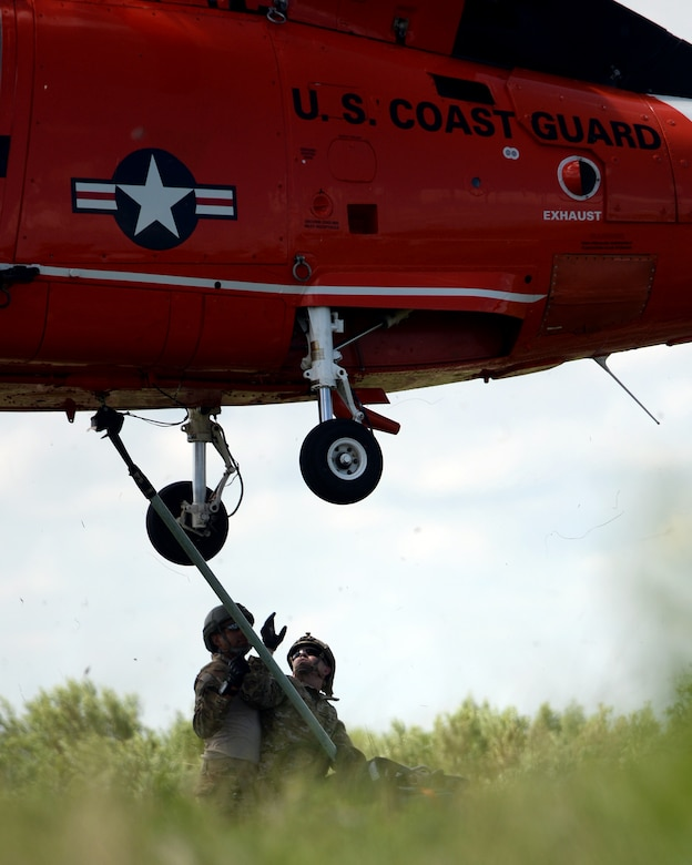Tactical Air Control Party members with the 147th Air Support Operations Squadron; 147th Reconnaissance Wing, perform sling load operations with a U.S. Coast Guard MH-65 Dauphin during a domestic response resupply exercise June 7, 2014, at Galveston State Park. With the 2014 hurricane season underway, the training allowed the TACPs to exercise response efforts with the Coast Guard members, performing helicopter landing zone operations, aerial resupply and sling load operations.