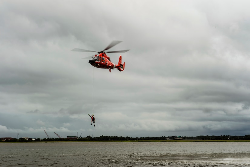 A Coast Guard HH-65 Dolphin pulls a rescue swimmer from the water during a demonstration  Aug. 4, 2014, at U.S.C.G. Sector Charleston, S.C. The demonstration showed the Coast Guard's rescue capabilities during the Coast Guard's 224th birthday celebration. (U.S. Air Force photo/Senior Airman George Goslin)