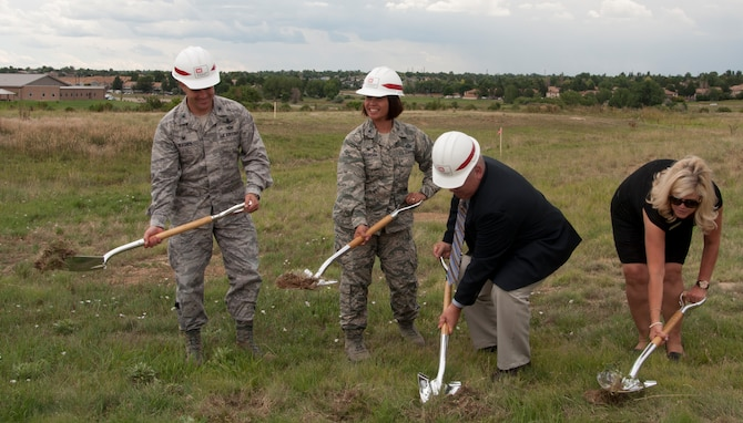 From left, Col. John Wagner, 460th Space Wing commander; Col. Rose Jourdan, 460th Mission Support Group commander; Al Woolley, 460th Force Support Squadron director; and Cindy Stark, 460th Force Support Squadron family member programs chief, break ground for a new accessible community park near the chapel Aug. 5, 2014, at the chapel on Buckley Air Force Base, Colo. The groundbreaking ceremony also included mention of a new accessible playground set to replace a current playground area. The projects, which are estimated to cost approximately $500,000, are scheduled to be complete in September.  (U.S. Air Force photo by Tech. Sgt. Kali L. Gradishar/Released)