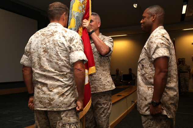 U.S. Marine Corps Maj. Gen. Mark. A. Clark, the outgoing Marine Corps Forces Special Operations Command commander, passes the Marine Corps colors to Maj. Gen. Joseph L. Osterman, the incoming MARSOC commander, during a change of command ceremony aboard Stone Bay at Camp Lejeune, N.C., Aug 6, 2014.
