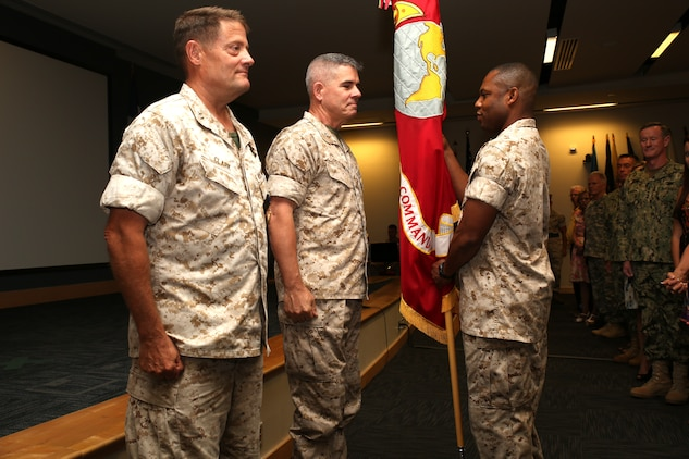 U.S. Marine Corps Sgt. Major John W. Scott passes the Marine Corps colors from Maj. Gen. Mark A. Clark, the outgoing Marine Corps Forces Special Operations Command commander, to Maj. Gen. Joseph L. Osterman, the incoming MARSOC commander, during a change of command ceremony aboard Stone Bay at Camp Lejeune, N.C., Aug 6, 2014.