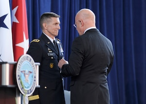 Director of National Intelligence James Clapper awards DIA Director Lt. Gen. Michael Flynn the National Intelligence Distinguished Service Medal during Flynn's retirement ceremony Aug. 7.
