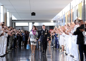 Lt. Gen. Michael Flynn exits DIA Headquarters with his wife, Lori, following his retirement ceremony Aug. 7. Military and civilian members of the workforce lined the hallway to wish the Flynns a fond final farewell.