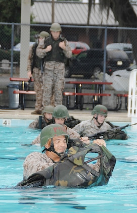 Master Sgt. Mark Carabello (front) operations and training chief, S-3, Operations and Training Division, Marine Corps Logistics Base Albany, sheds his gear and uses it as a floatation device during the annual swim qualification at the Base Pool, Aug. 1.