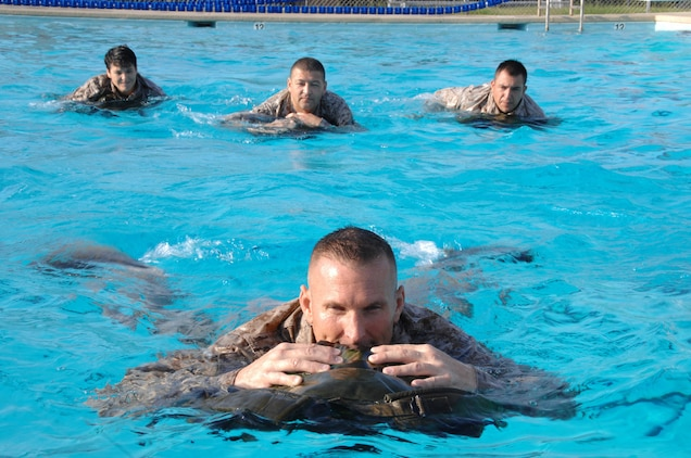 Marines use their packs as floatation devices during their annual swim qualification at Marine Corps Logistics Base Albany's Base Pool, July 28 – Aug. 1. Ninety-eight Marines completed their training with 72 earning the Water Survival-Basic qualification and 26 receiving the Water Survival-Intermediate qualification.