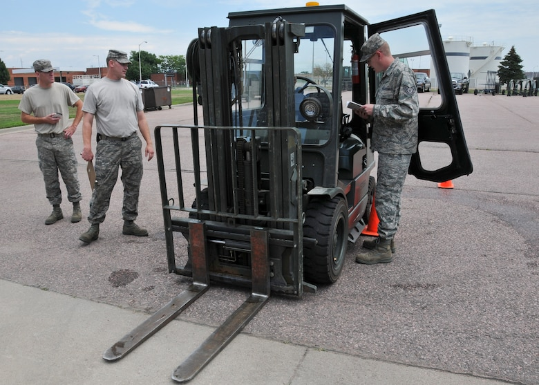 Tech. Sgt. Kyle Sorenson, 114th Logistics Readiness Squadron mobility specialist, performs pre-use inspection procedures as he participates in LRS's forklift rodeo at Joe Foss Field, S.D, on Aug. 2, 2014. The rodeo tested the participant's communication and driving skills as they navigated machinery holding a full bucket of water through an obstacle course while attempting to lose the minimum amount of water in transit. (National Guard photo by Staff Sgt. Luke Olson/Released)