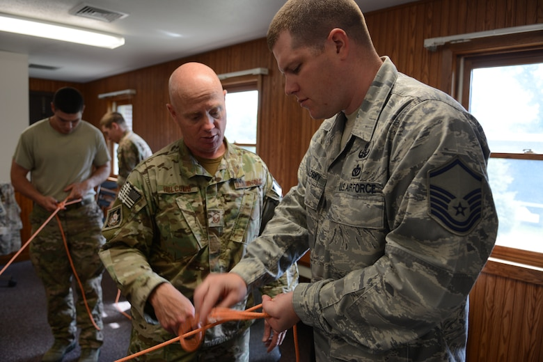 Master Sgt. Gilbert E. Holcomb, 115th Fighter Wing explosive ordnance disposal flight resources non-commissioned officer in-charge, teaches EOD Airmen how to tie proper knots during the 2014 PATRIOT exercise at Volk Field Air National Guard Base, Wis., July 20, 2014. The team later used their knot-tying skills to safely lower themselves down a three-story building. (Air National Guard photo by Senior Airman Andrea F. Liechti)