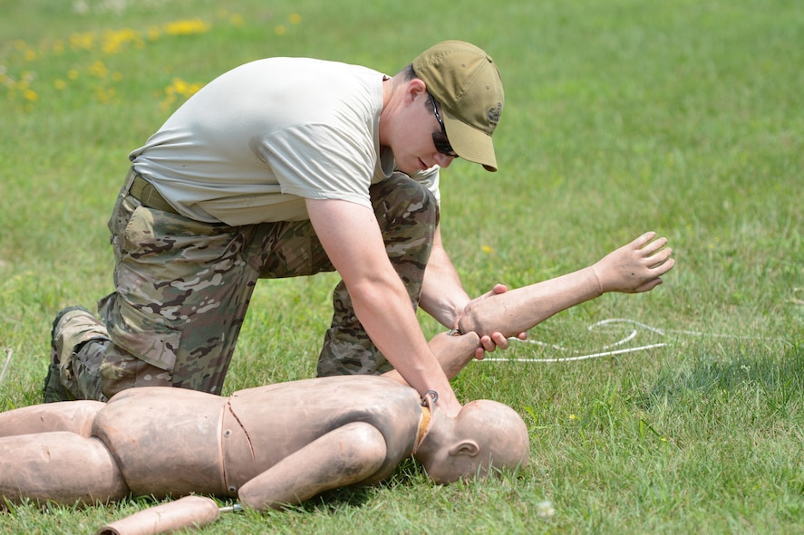 Senior Airman John R. Tourtellotte, 104th Fighter Wing explosive ordnance disposal flight, practices safely turning a body over during the EOD hook-and-line class at the 2014 PATRIOT exercise at Volk Field Air National Guard Base, Wis., July 20, 2014. Along with hook-and-line procedures, the EOD Airmen learned how to tie proper knots for rappelling, participated in fast rope exercises, climbed a free-falling ladder, assembled and disassembled various bomb types, and received all-terrain vehicle training certification. (Air National Guard photo by Senior Airman Andrea F. Liechti)