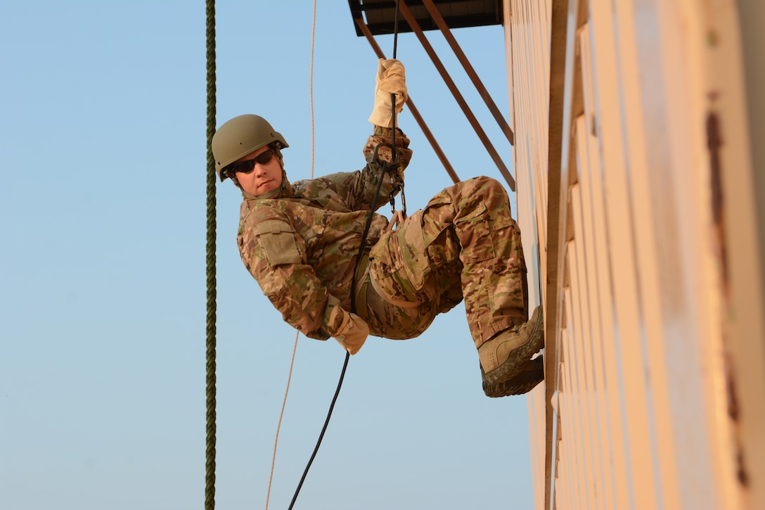 Master Sgt. Jeremiah W. McClosky, 104th Fighter Wing explosive ordnance disposal flight, rappels down a three-story building during the 2014 PATRIOT exercise at Volk Field Air National Guard Base, Wis., July 20, 2014. The EOD Airmen learned how to tie proper knots for rappelling, participated in fast rope exercises, climbed a free-falling ladder, assembled and disassembled various bomb types, and received all-terrain vehicle training certification during their stay. (Air National Guard photo by Senior Airman Andrea F. Liechti)