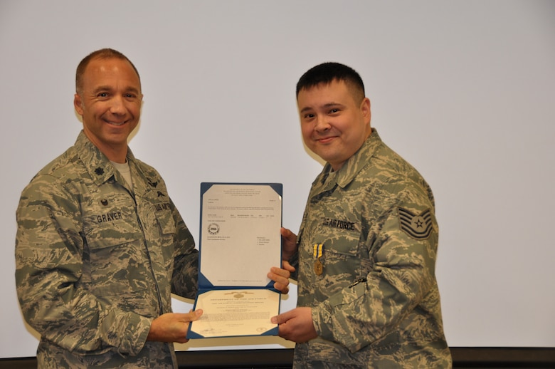 Lt. Col. John Graver, 304th Rescue Squadron commander, presents Tech. Sgt. Carl Valentine the Air Force Commendation Medal, Aug. 2, 2014. The 304th RQS is trained and equipped to deploy combat rescue officers, pararescuemen, and support personnel worldwide in support of U.S. national security interests. (U.S. Air Force photo/Staff Sgt. Daniel Delgado)