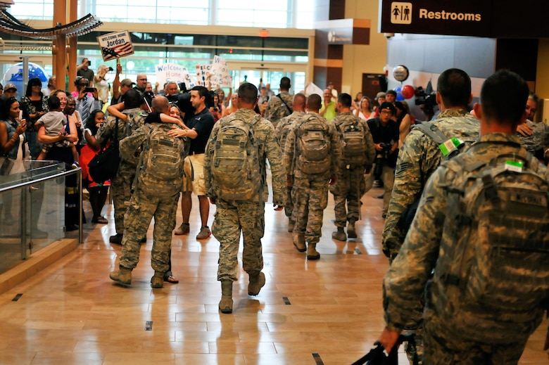 Airmen with the 182nd Security Forces Squadron reunite with family and friends after arriving home at the General Wayne A. Downing Peoria International Airport in Peoria, Ill., Aug. 6, 2014. The Illinois Air National Guardsmen deployed to Southwest Asia for seven months in support of Operation Enduring Freedom. They were assigned to the 405th Expeditionary Security Forces Squadron overseas, where they were responsible for law enforcement and security missions in the region's global war on terror. (U.S. Air National Guard photo by Staff Sgt. Lealan Buehrer/Released)