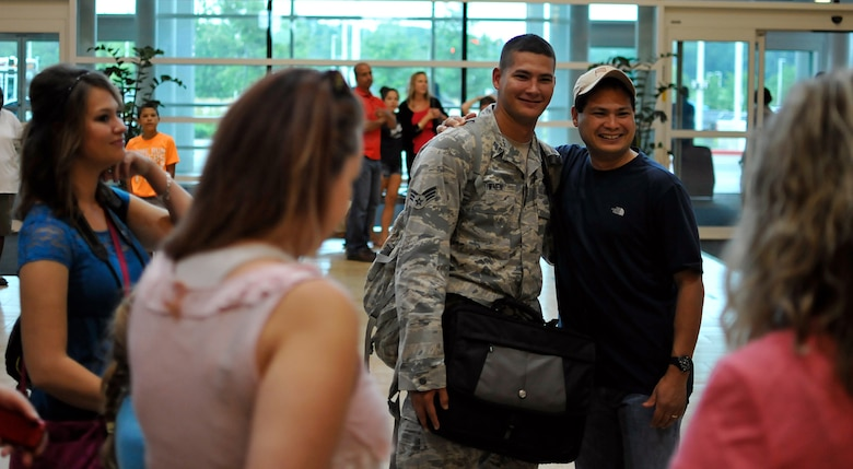 U.S. Air Force Senior Airman Christian A. Downen of the 182nd Security Forces Squadron, reunites with family and friends after arriving home at the General Wayne A. Downing Peoria International Airport in Peoria, Ill., Aug. 6, 2014. He and 17 Illinois Air National Guardsmen deployed to Southwest Asia for seven months in support of Operation Enduring Freedom. They were assigned to the 405th Expeditionary Security Forces Squadron overseas, where they were responsible for law enforcement and security missions in the region's global war on terror. (U.S. Air National Guard photo by Staff Sgt. Lealan Buehrer/Released)