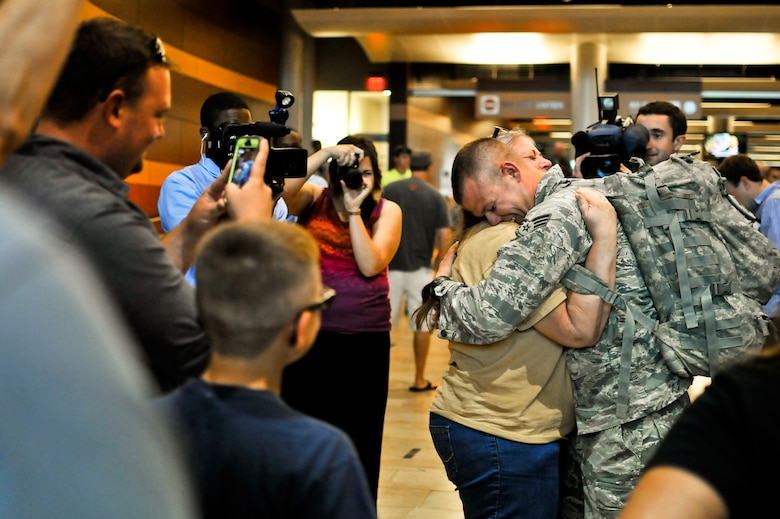 U.S. Air Force Senior Airman Samuel C. Smith, security forces journeyman with the 182nd Security Forces Squadron, reunites with family and friends after arriving home at the General Wayne A. Downing Peoria International Airport in Peoria, Ill., Aug. 6, 2014. He and 17 Illinois Air National Guardsmen deployed to Southwest Asia for seven months in support of Operation Enduring Freedom. They were assigned to the 405th Expeditionary Security Forces Squadron overseas, where they were responsible for law enforcement and security missions in the region's global war on terror. (U.S. Air National Guard photo by Staff Sgt. Lealan Buehrer/Released)