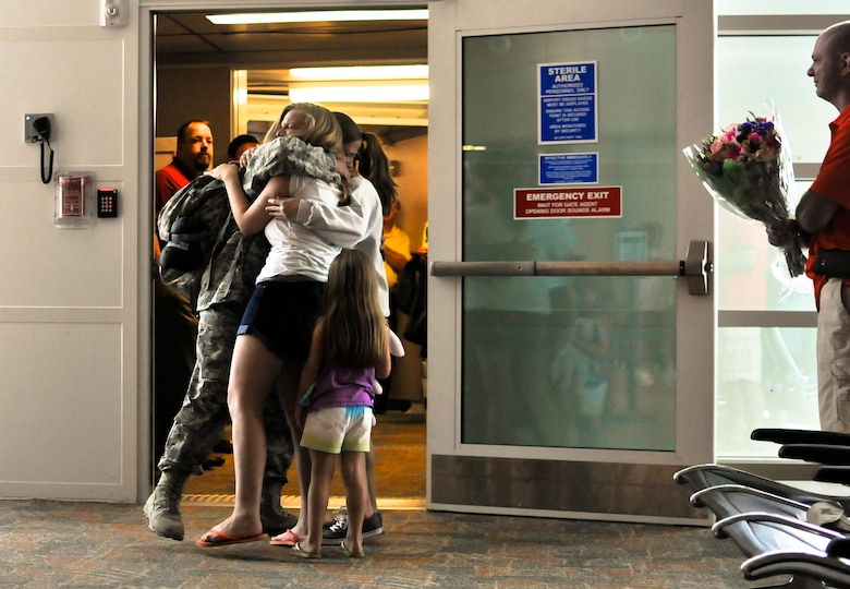 U.S. Air Force Tech. Sgt. Stacy A. Merdian, security forces craftsman with the 182nd Security Forces Squadron, reunites with family and friends after arriving home at the General Wayne A. Downing Peoria International Airport in Peoria, Ill., Aug. 6, 2014. She and 17 Illinois Air National Guardsmen deployed to Southwest Asia for seven months in support of Operation Enduring Freedom. They were assigned to the 405th Expeditionary Security Forces Squadron overseas, where they were responsible for law enforcement and security missions in the region's global war on terror. (U.S. Air National Guard photo by Staff Sgt. Lealan Buehrer/Released)