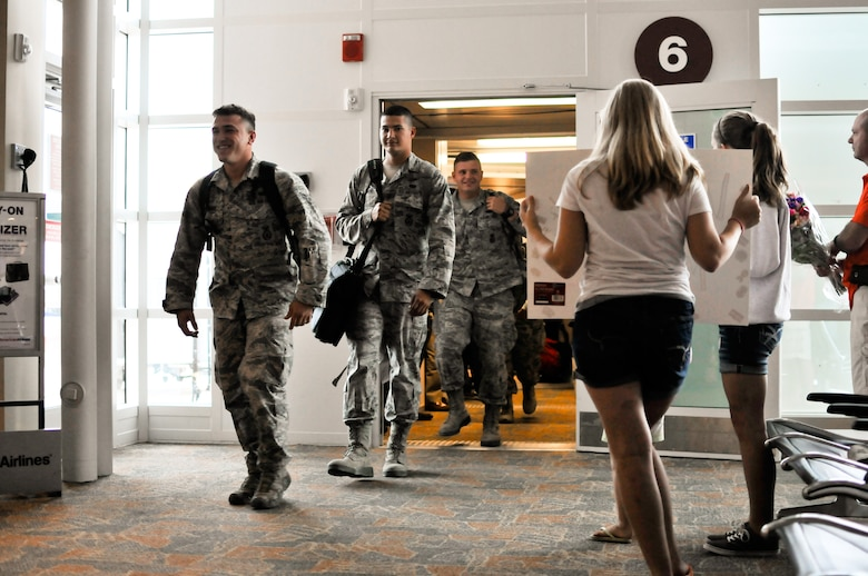 From left, U.S. Air Force Airman 1st Class Tyler N. Woolridge, Senior Airman Christian A. Downen and Airman 1st Class Jordan A.D. Sanford, specialists with the 182nd Security Forces Squadron, arrive home at the General Wayne A. Downing Peoria International Airport in Peoria, Ill., Aug. 6, 2014. They and 15 Illinois Air National Guardsmen deployed to Southwest Asia for seven months in support of Operation Enduring Freedom. They were assigned to the 405th Expeditionary Security Forces Squadron overseas, where they were responsible for law enforcement and security missions in the region's global war on terror. (U.S. Air National Guard photo by Staff Sgt. Lealan Buehrer/Released)
