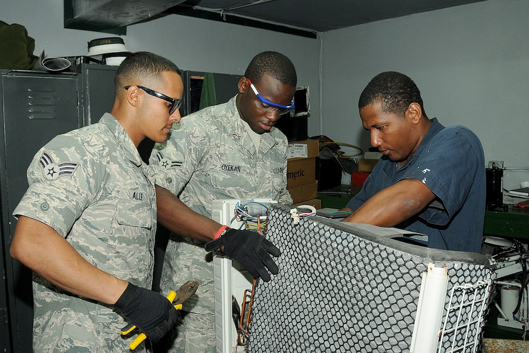 Senior Airman Christian Dario Alee (left), Airman First Class Oluwatomisin Nmn Oyekan of the Rhode Island Air National Guard,143d Airlift Wing, Civil Engineering Squadron, replaces the compressor of an air conditioning unit with their  Bahamian counterpart Marine Mechanic Neil Nairn of the Royal Bahamas Defence Force (RBDF), HVAC shop at the Coral Harbour Base in Nassau, Bahamas on June 16, 2014 for their inaugural group DFT (Deployment For Training) to support the RBDF in conjunction with the National Guard State Partnership Program (SPP). National Guard Photo by Master Sgt John McDonald (RELEASED)