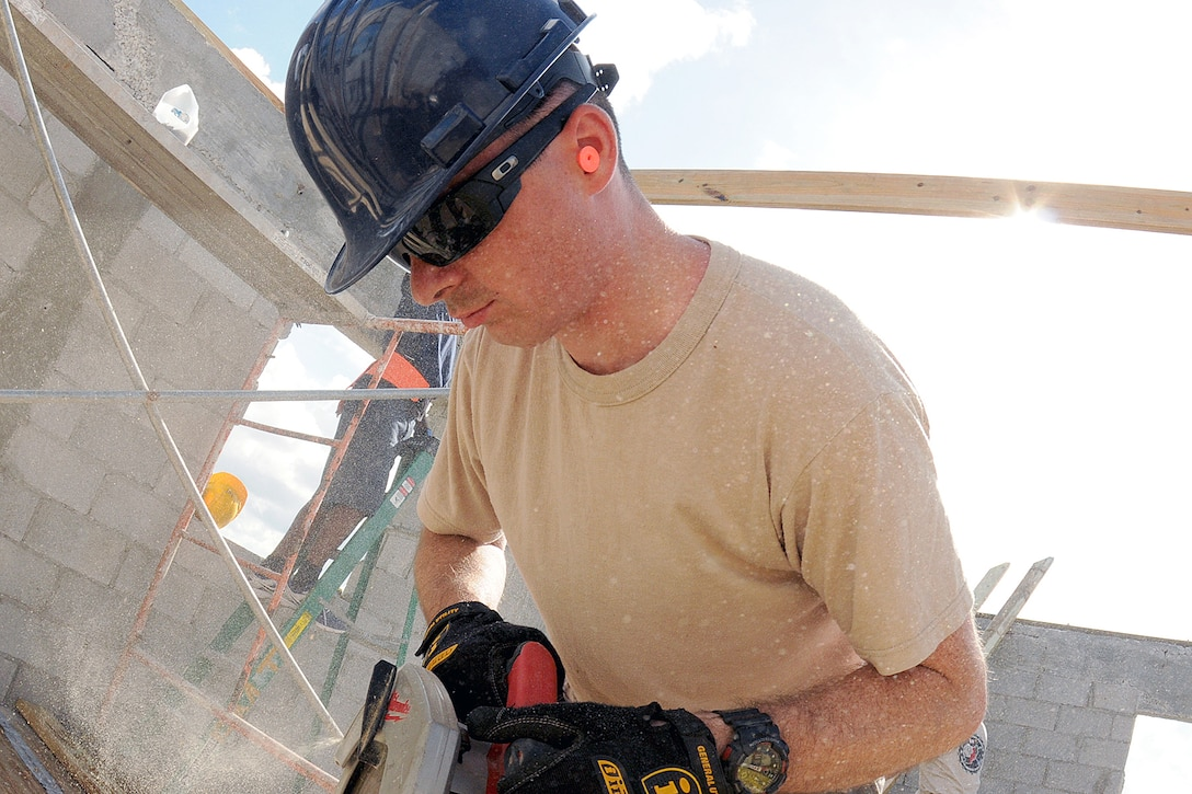 Senior Airman Daniel Douglas Tift, of the Rhode Island Air National Guard,143d Airlift Wing, Civil Engineering Squadron Structures Shop saws joists to a new roof for the women's barracks and latrine for the Royal Bahamas Defence Force (RBDF) at the Coral Harbour Base in Nassau, Bahamas on June 17, 2014 for their inaugural group DFT (Deployment For Training) to support the RBDF in conjunction with the National Guard State Partnership Program (SPP). National Guard Photo by Master Sgt John McDonald (RELEASED)