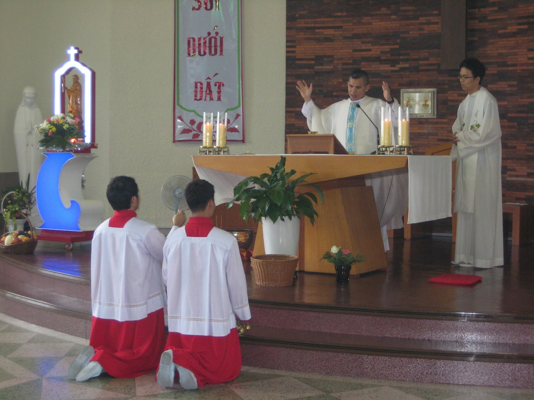Chaplain (Capt.) Thienan Tran, 51st Fighter Wing chaplain, leads his church in prayer during a Catholic Mass while altar servers kneel to prepare incense at Cho-Rang Catholic Church in Busan, Republic of Korea Aug. 3, 2014. Tran spends his off-duty time providing Catholic Mass to communities of Vietnamese labor workers.