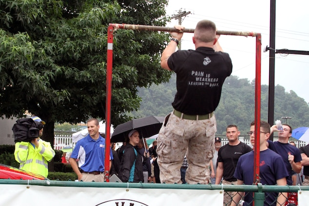 U.S. Marine Corps Staff Sgt.  Joshua Young, recruiter at Permanent Contact Station Ohio Valley, Recruiting Sub-Station Zanesville, demonstrates the proper form for pull-ups during the 69th Annual Rudy Mumley Ohio Valley Athletic Conference All-Star football game in Wheeling, Ohio, July 27, 2014. Local NBC affiliate WTOV-9 filmed the demonstration during their live coverage of the game that showcased high school talent from Ohio and West Virginia. (U.S. Marine Corps photo by Sgt. T.M. Stewman/Released)