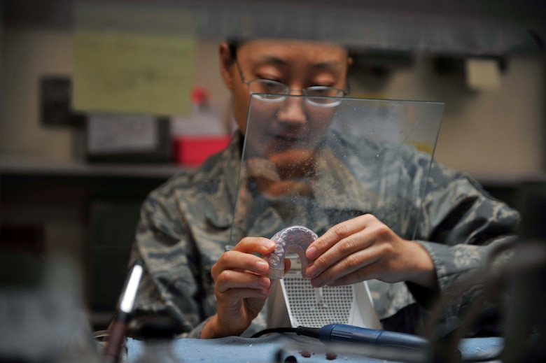 Staff Sgt. Janine Sung places a bilaminate mouth guard onto its tooth mold to ensure it fits properly on Osan Air Base, Republic of Korea, July 29, 2014. Sung is a laboratory technician with the 51st Dental Squadron. Mouth guards are used to protect the teeth from grinding or if the patient has other jaw-related issues. (U.S. Air Force photo/Senior Airman David Owsianka)