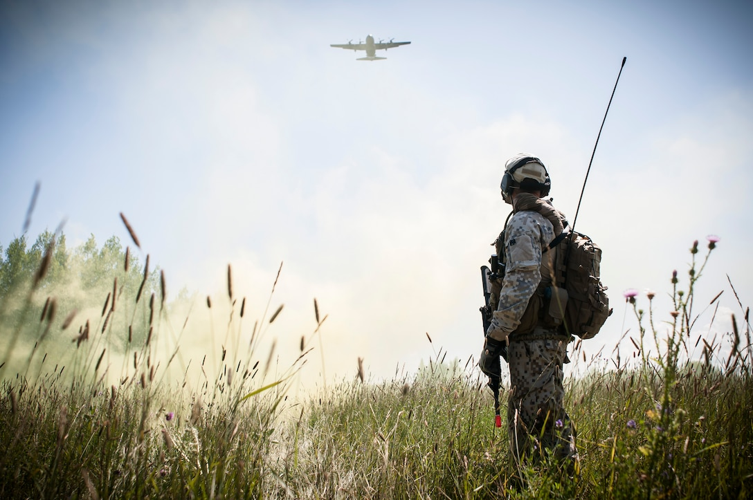 Capt. Armands Rutkis, a Joint Tactical Air Controller from the Latvian armed forces, marks a drop zone with smoke to allow a C-130 Hercules to drop simulated cargo during Operation Northern Strike 2014 near Rogers City, Mich. on Aug. 5, 2014. The C-130 is based with the 182nd Airlift Wing in Peoria, Ill. Operation Northern Strike 2014 is a joint multi-national combined arms training exercise conducted in Michigan. (U.S. Air National Guard photo/Master Sgt. Scott Thompson)